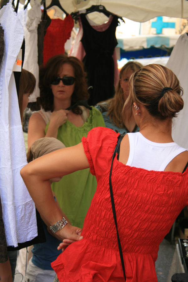 Discussion entre femmes sur un stand de robes sur le marché d'Orange.